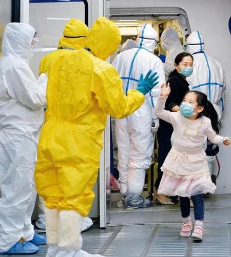 乘坐东方航空公司包机从新加坡回武汉的一名刚下飞机的小姑娘跟地服人员打招呼